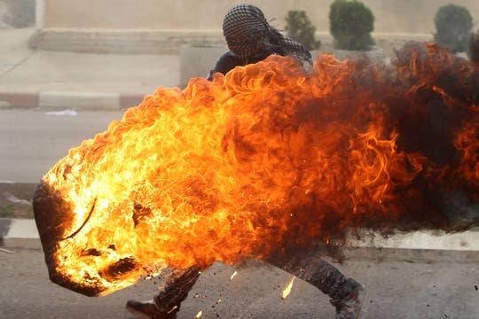 Un estudiante palestino de la Universidad de Birzeit empuja un neumático en llamas durante los enfrentamientos con soldados israelíes. Foto: AFP