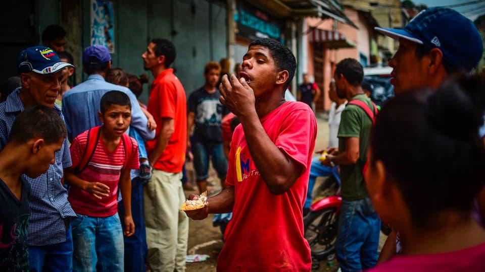 Un chico come comida que encontró afuera de uno de los locales saqueados anoche. Foto: AFP / Ronaldo Schemidt