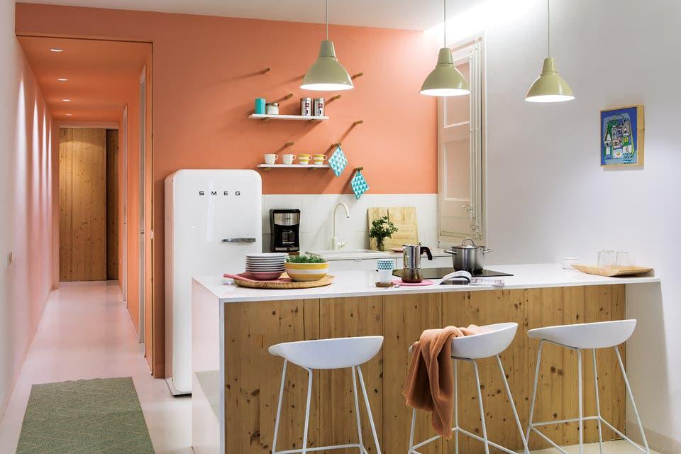 Surge de la alzada, pero pareciera que toda la cocina es color salmón. Continúa en un pasillo que causa sensación con lo mínimo: una pared, el cielo raso y spots que tiñen el blanco .  /Gentileza Enrique Menossi