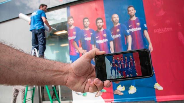 Un hombre sostiene su teléfono móvil con una foto de un cartel con el delantero brasileño Neymar tras ser reemplazado por otro cartel fuera del Estadio Camp Nou en Barcelona