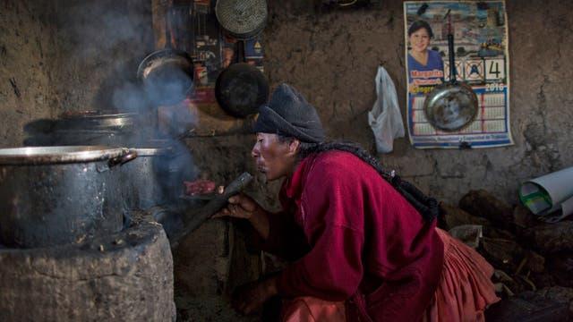 Lilian Ávila Díaz enciende su estufa de leña para preparar el almuerzo para su familia en Coata, un pequeño pueblo a orillas del lago Titicaca, en la región de Puno, Perú
