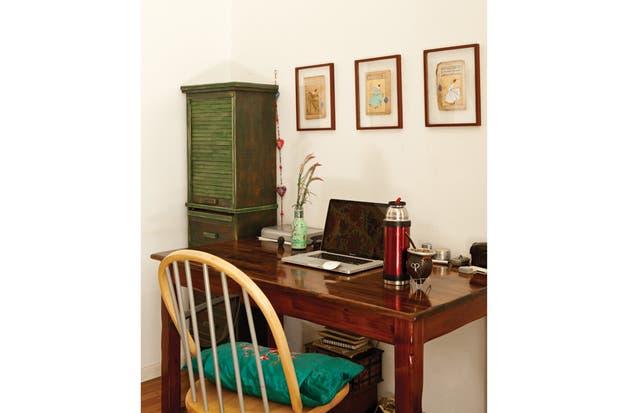 Una zona de trabajo con escritorio diseñado por Ana Martín, silla FOA ($2.530, Dash), ropero antiguo (desde $1.200, Mercado de Pulgas) y tres cuadritos con caligrafía dorada de Estambul..