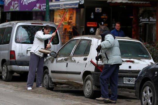Dos hombres limpian los autos que se encuentran tapados de cenizas. Foto: Reuters