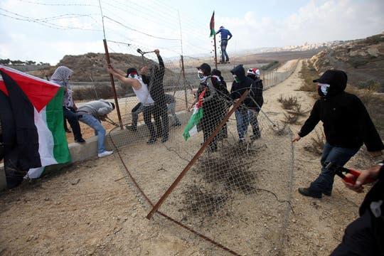 Jóvenes palestinos cortan un alambrado en la aldea cisjordana de Ramallah. Foto: AFP
