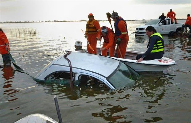 Los bomberos rescatan el Chevrolet Celta del comerciante desaparecido, que estaba en el fondo de una laguna