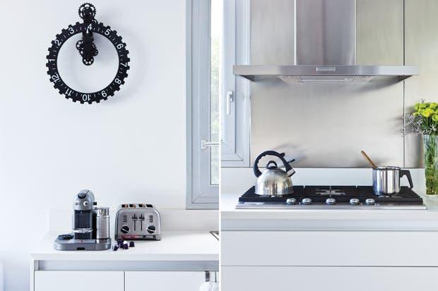 """Esta cocina es multifuncional. Mientras se cocina, los invitados pueden estar en el living disfrutando una picada, jugando un campeonato con la consola o mirando una película"""". Junto a la cafetera Nespresso, reloj de pared traído de un viaje.  /Javier Picerno"""