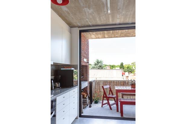 Como una continuación casi perfecta del living (tiene el mismo piso de cemento alisado e idéntico techo de hormigón visto), el balcón se acondicionó con una mesa pintada de rojo donde pueden comer cómodamente sentadas hasta ocho personas.  /Daniel Karp