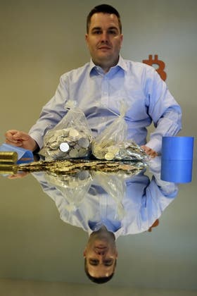 Mike Caldwell junto a sus monedas Bitcoin, acuñadas en su casa