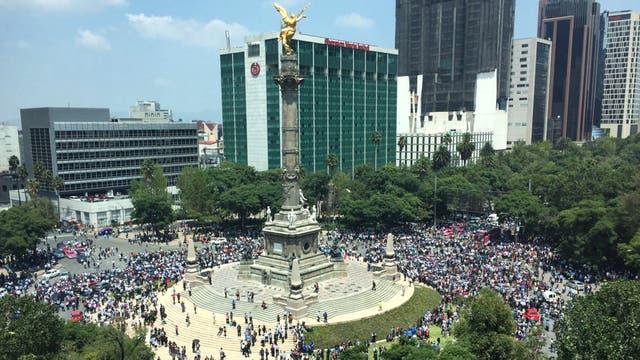 La gente se junta alrededor de El Angel de la Independencia en la Ciudad de México. Foto: AP / Enric Marti
