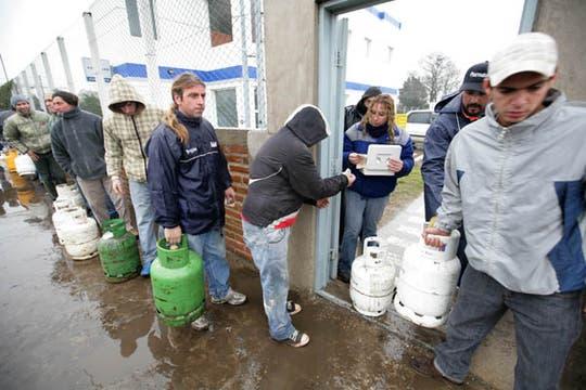 Bajo el agua y el frío gran cantidad de personas hacen cola para poder comprar una garrafa. Foto: LA NACION / Mauro V. Rizzi