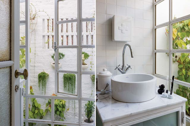 Hacia el patio, un ventanal de vidrio repartido hasta el piso. El blanco domina la escena por completo: azulejos en paredes y piso, un peque?o mueble con frente de vidrio esmerilado, mesada y bacha redonda. En lugar de espejo, un botiquín metálico (Gato Store)