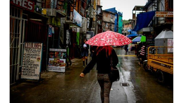 Una mujer camina a través de la Villa 31 un día nublado