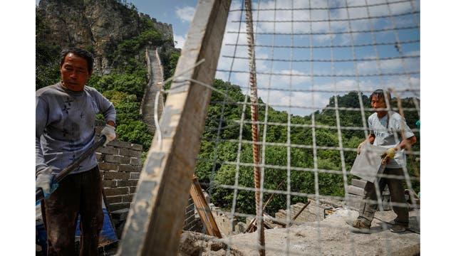 Obreros trabajando en la reconstrucción de la sección Jiankou de la Gran Muralla, ubicada en el distrito de Huairou, al norte de Pekín