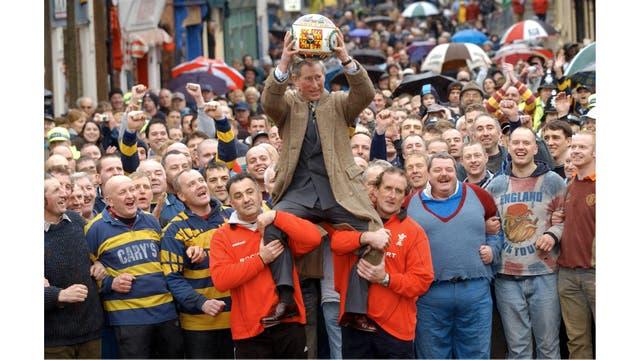 Jugadores lo levantan mientras muestra el balón oficial de un evento deportivo