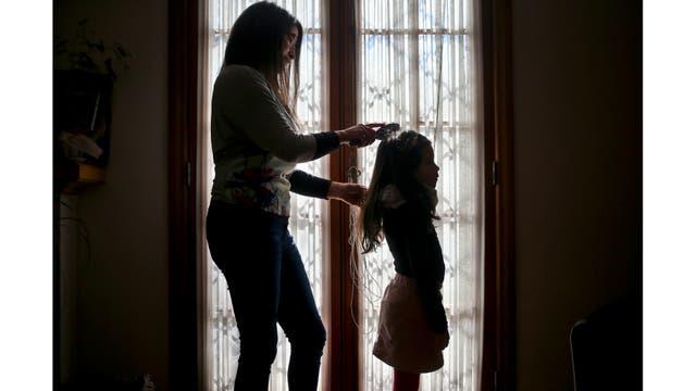 Monica Flores peina el cabello de su hija en su casa en Santiago, Chile.