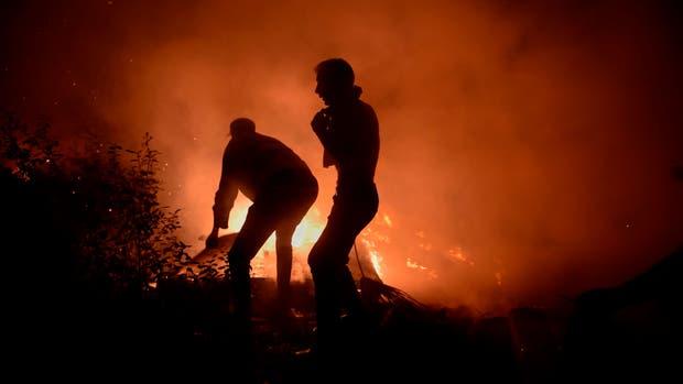 Decenas de bomberos y vecinos luchas contra las llamas que azotan la región de Galicia, España