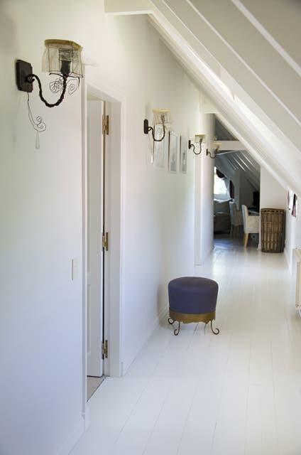 El piso blanco y brillante continúa en el luminoso corredor que lleva a la suite principal..  Foto:Living /Mauro Ramírez