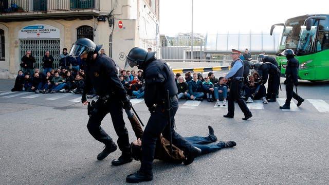 Policías regionales catalanes (Mossos d'Esquadra) arrastran a un piquetero que bloquea la calle en la estación de autobuses Norte de Barcelona