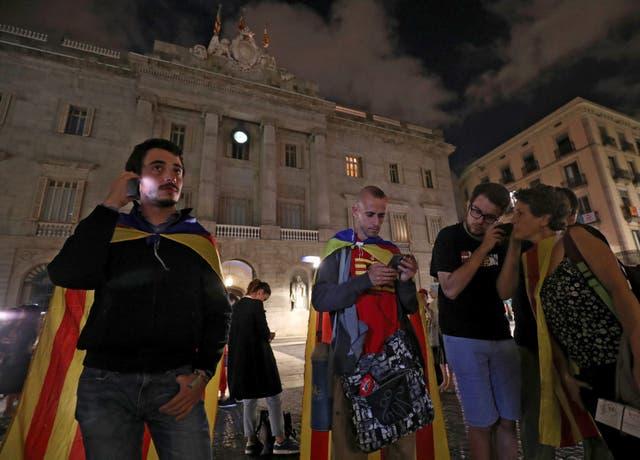 Catalanes escuchan el discurso envueltos en banderas independentistas