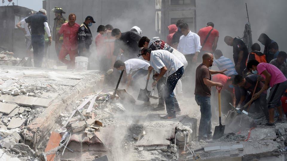 Bomberos, rescatistas y civiles trabajan para remover los escombros. Foto: AFP