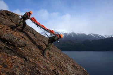 Dos de los gendarmes demuestran cómo es la técnica para descender por la pared de una montaña cargando una persona en una camilla.