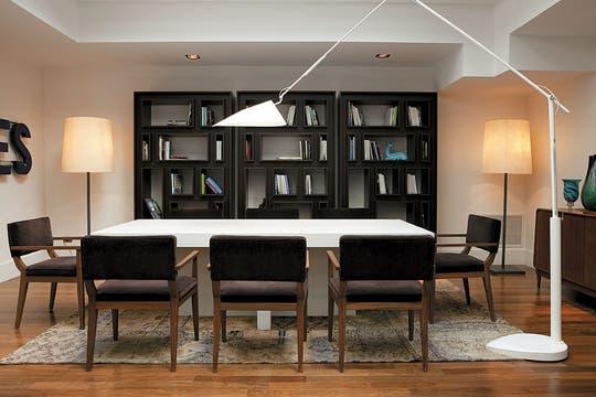 La biblioteca, muy bien provista, comparte espacio con muebles funcionales y de estilo contemporáneo, y otros antiguos. También la alfombra sostiene el concepto que mezcla lo clásico y lo moderno. Foto: Adela Aldama