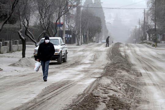 Un hombre con barbijo camina por las calles de Bariloche cubiertas de ceniza. Foto: Reuters