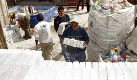 Los operarios cargan un camión con ladrillos ecológicos con destino a Unquillo