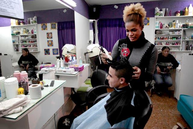 Constitución: la dominicana María Isabel Berroa deja a punto el degradé en el pelo de un cliente