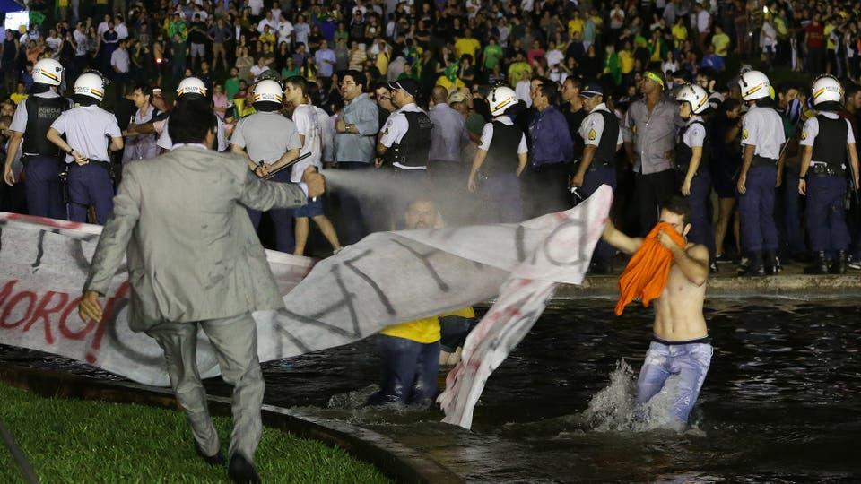 Un policía de civil arroja gas pimienta a un manifestante. Foto: AP