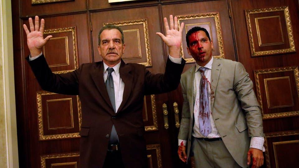 El legislador de la oposición Stefanelli gesticula junto a su colega Leonardo Regnault, luego de que un grupo de partidarios del gobierno irrumpió en la Asamblea Nacional. Foto: Reuters / Carlos Garcia Rawlins