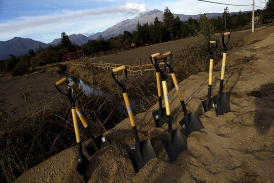 La capa de ceniza cubre los caminos; vecinos y soldados trabajan con palas para despejarlos. Foto: Reuters