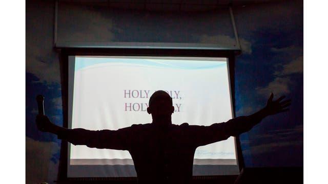 El pastor Fabio de Souza reza durante el servicio dominical