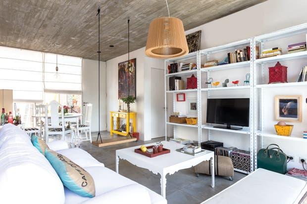 La pared casi completa se aprovechó con un mueble metálico de grandes dimensiones para alojar la pantalla, revistas, libros y objetos de diseño.  /Daniel Karp