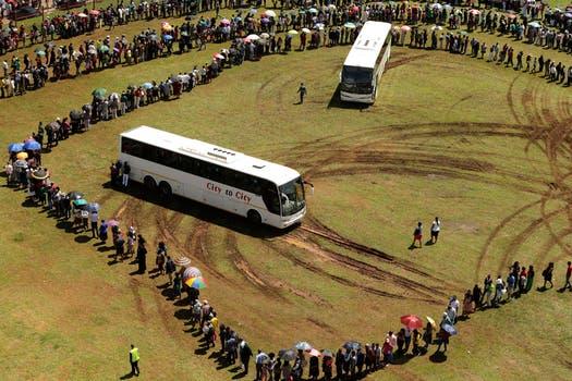 Miles de personas hacen cola para tomar un colectivo para poder ir a a despedir a Mandela en la Sede de Gobierno Sudafricano. Foto: AP