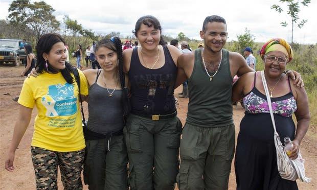 Un guerrillero abrazado por su madre camina con otros rebeldes por los Llanos del Yar, lugar de la cumbre de las FARC