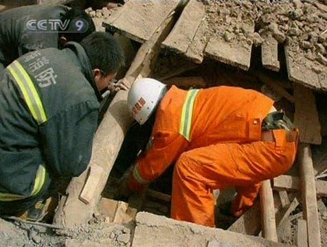Imagen de la televisión estatal china CCTV muestra a los rescatistas intentado sacar de entre los escombros a un sobreviviente. Foto: AFP