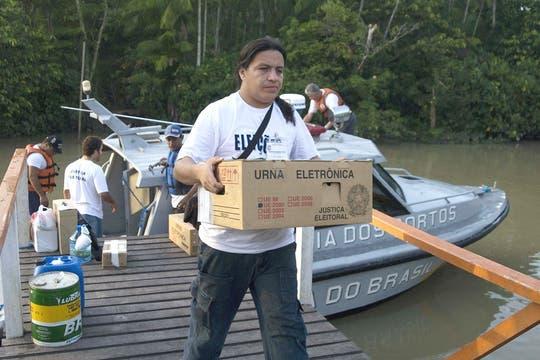Encargados del operativo de elecciones llegan en bote a las comunidades aisladas de la isla de Periquitaquara en el Amazonas. Foto: Reuters