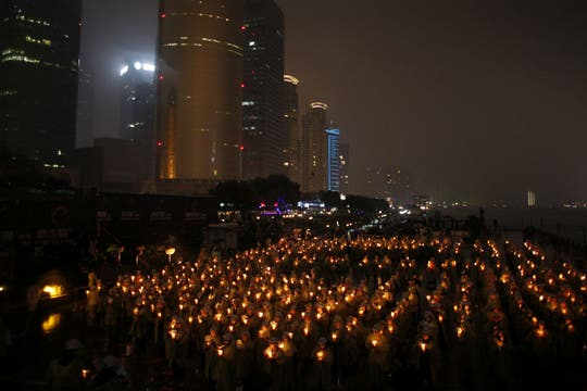 En China, intentan romper el récord mundial de velas prendidas, mientras sus edificios estan a oscuras. Foto: Reuters