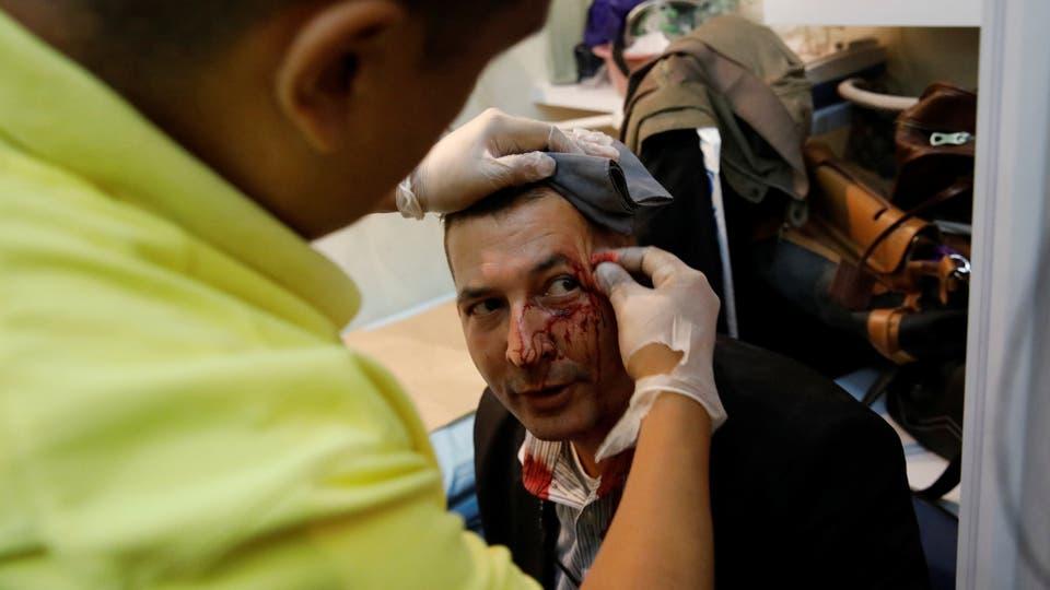 Un trabajador de la Asamblea Nacional siendo atendido por primeros auxilios. Foto: Reuters / Carlos Garcia Rawlins