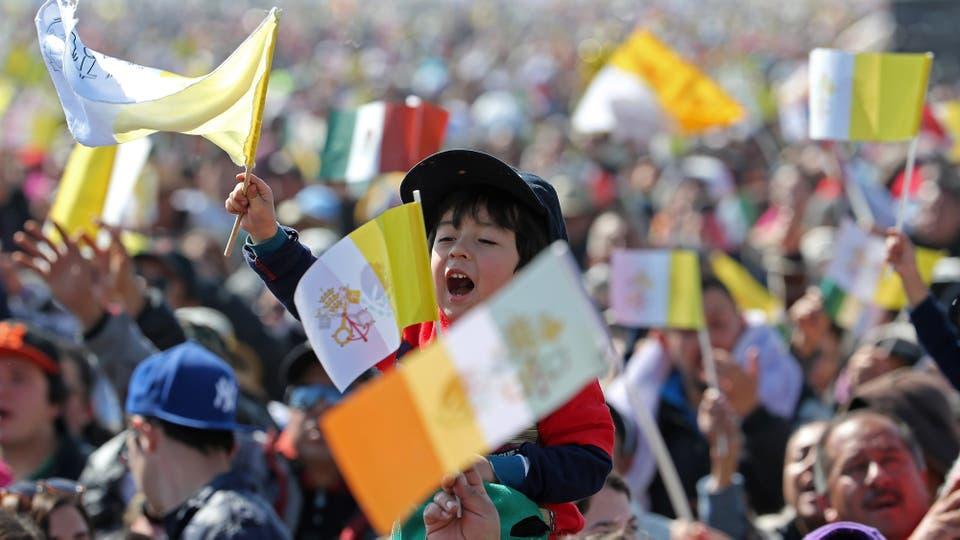 Un niño canta con una bandera del Vaticano en la mano, en Ecatpec, mientras espera la llegada del Papa. Foto: AP