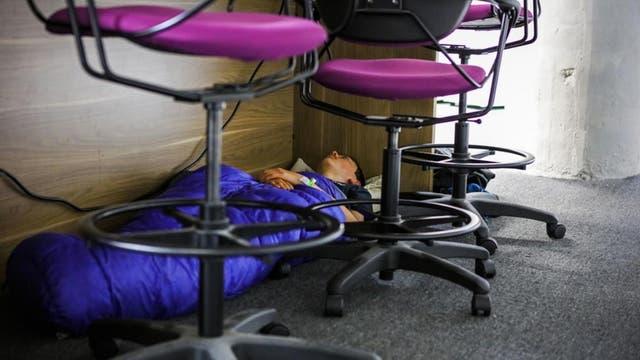 Un participante de Hackathón duerme debajo de un escritorio