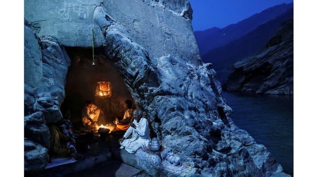 Sacerdotes hindúes se sientan dentro de una cueva mientras realizan oraciones vespertinas en las orillas del río Ganges en Devprayag