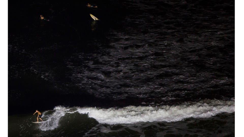 Luego de varias protestas y acampes en la playa para evitar el ensanche del camino nace el surf nocturno; la municipalidad igual ensanchó el camino costero. Foto: AP / Rodrigo Abd