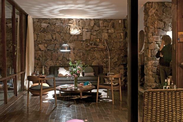 En el living con vista franca al exterior, sillón años 60 en jacquard con patas de bronce regulables (Olika). La lámpara Arco -un diseño de Achille Castiglioni, también de los 60-, ilumina la mesa del centro (todo de Olika).