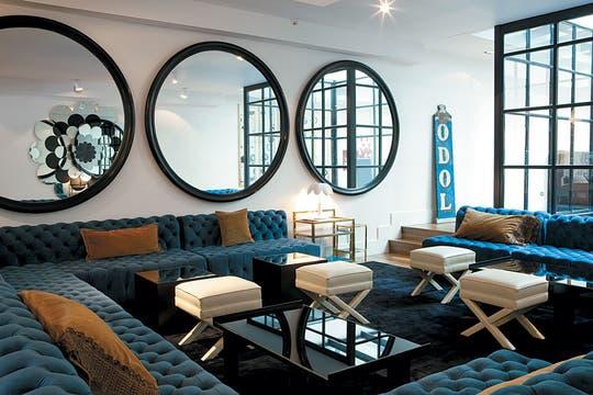 Sofás tipo Chesterfield (con tapizado en terciopelo azul) fijados a las paredes, conforman un gran living junto al bar. El espacio se flexibiliza con las banquetas blancas, dado que permiten ordenar la sala de diferentes maneras, de acuerdo con las necesidades. Foto: Adela Aldama