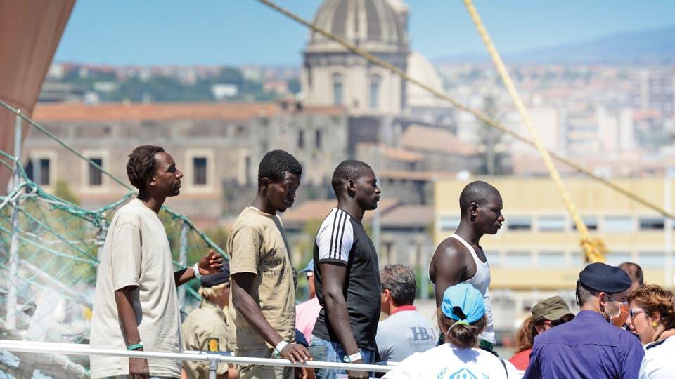 Migrantes aguardan el desembarco en Catania. Tras una larga travesía, deberán enfrentar el racismo y cuidarse también de las mafias africanas que crecen en el sur de Italia