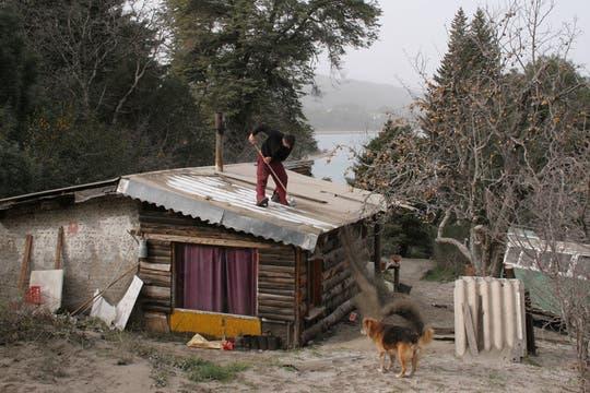 Un honmbre quita las cenizas del techo de su casa en Villa Campanario, cerca de Bariloche. Foto: AFP