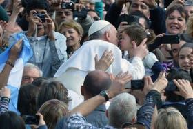 El Papa llegó en el papamóvil, saludó a los fieles y besó bebes
