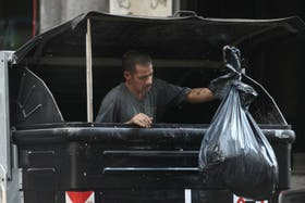 En pleno centro porteño, una persona llega al extremo de meterse en un tacho de basura en busca de comida
